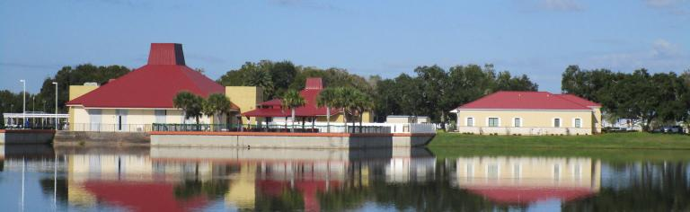 Photo of Adminstration Building taken from across the lake- Calm waters contain reflection of the building